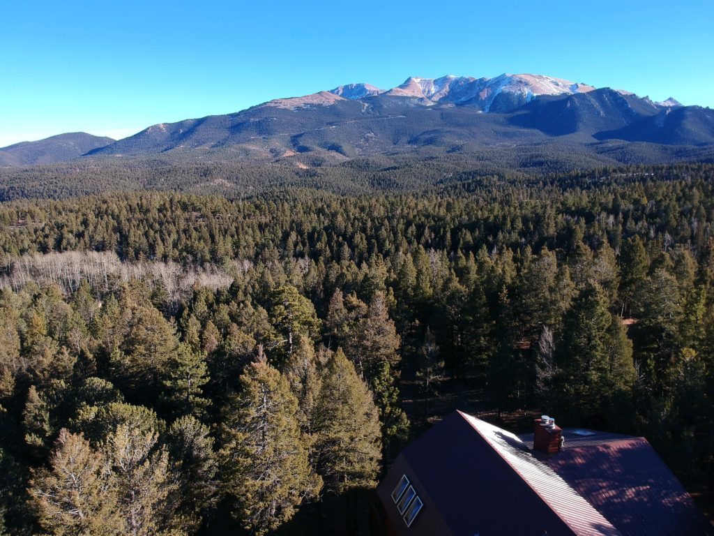 Pikes Peak rises up behind the cabin.